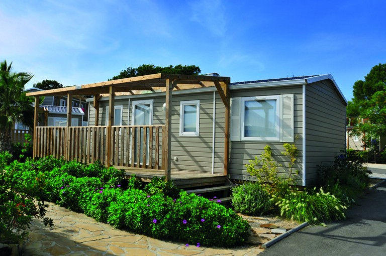 a nice mobile home with a wooden veranda in a campsite